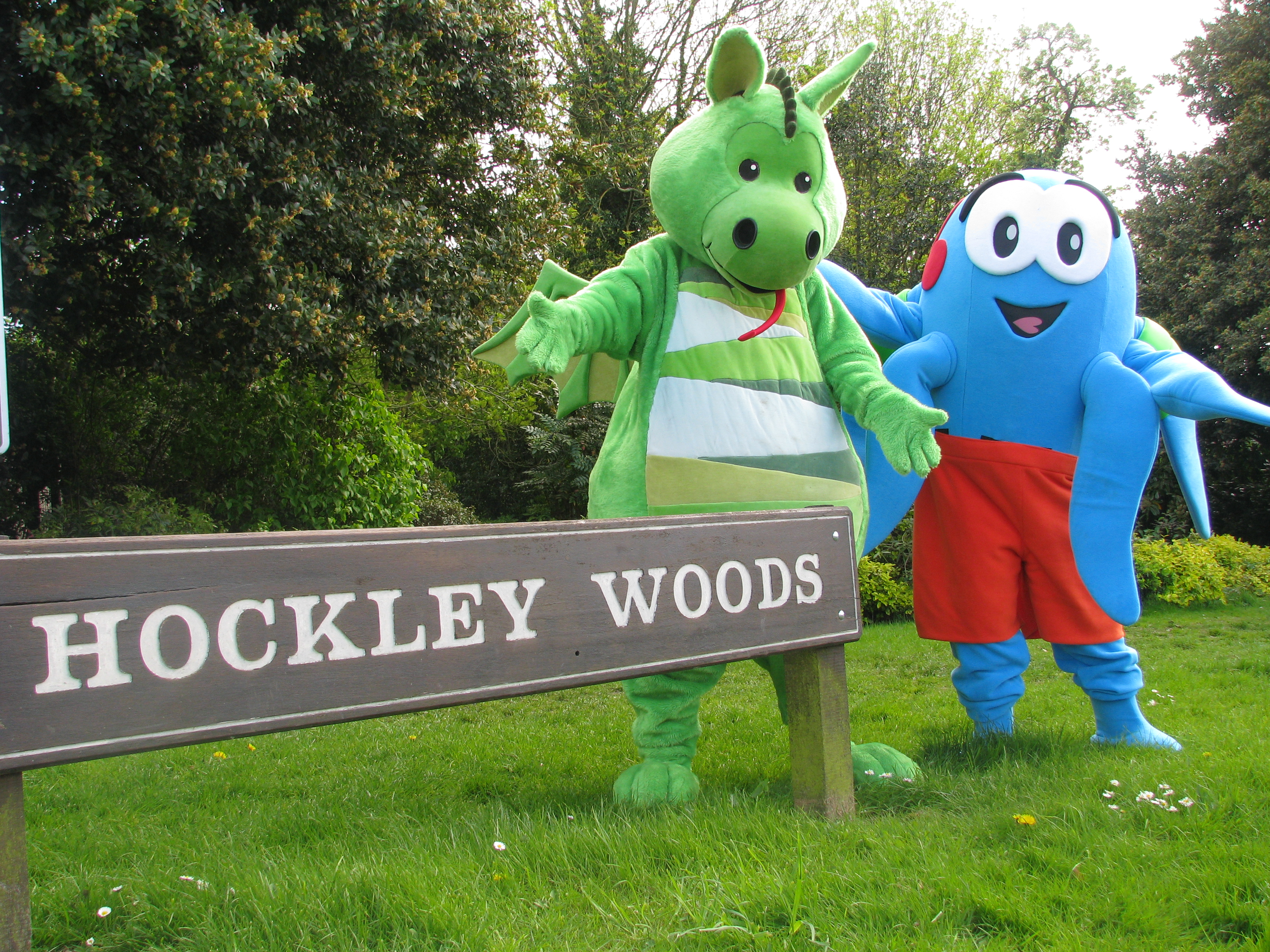 Image of Rochford District Council mascots standing besides Hockley Woods sign